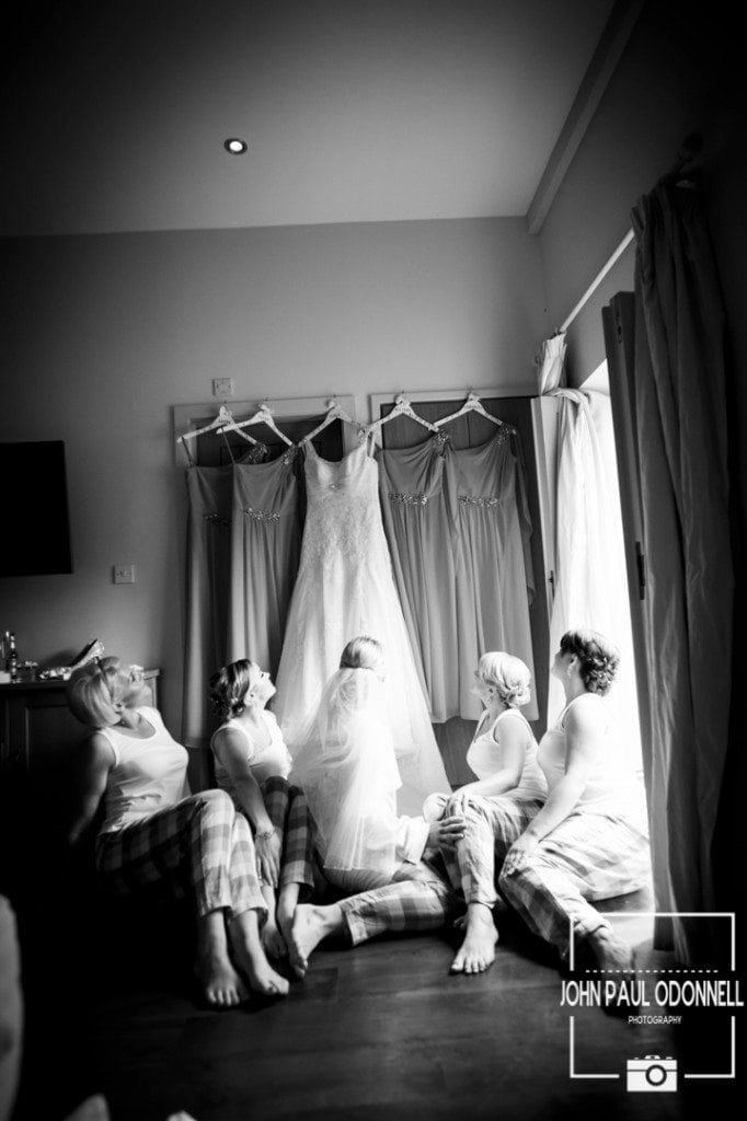 This is a picture taken of the bride with the bridesmaids sitting down and all looking up at the dresses