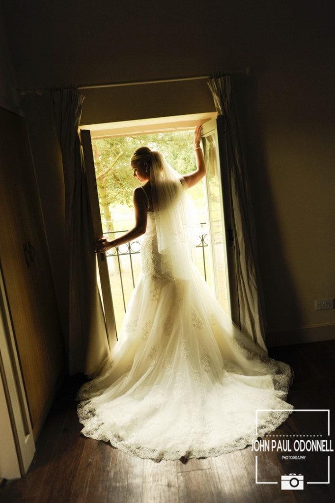 Reportage picture of the bride standing in the doorway with the sun coming through
