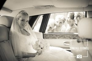 Bridesmaids peeping through the window of a Rolls royce Phantom