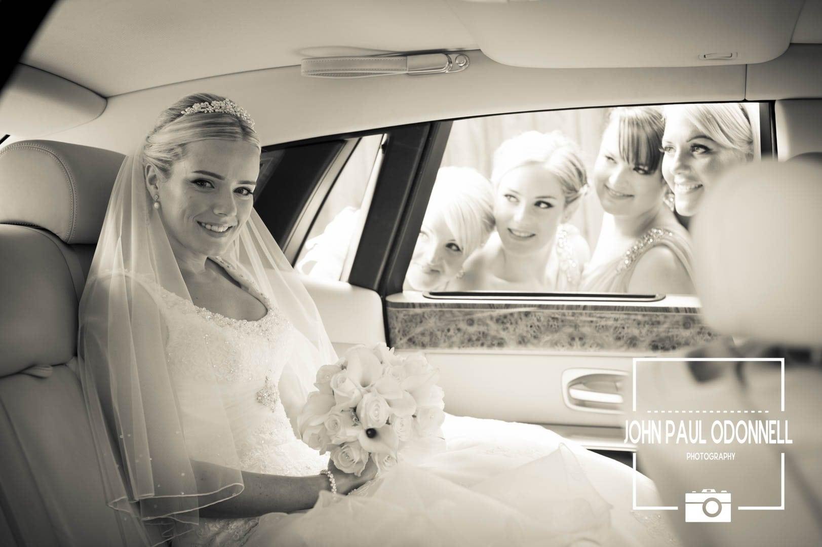 Bridesmaids peeping through the window of a Rolls royce Phantom