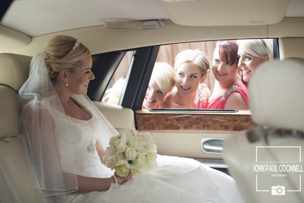 Reportage picture of a bride arriving at the church and her bridesmaids looking through the car window just before the ceremony