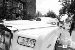 Bride and Groom posing at the rear of the wedding car reportage picture at Newland Hall