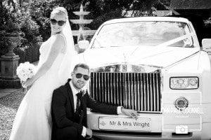 Bride and groom in a reportage picture with the car shot at Newland Hall