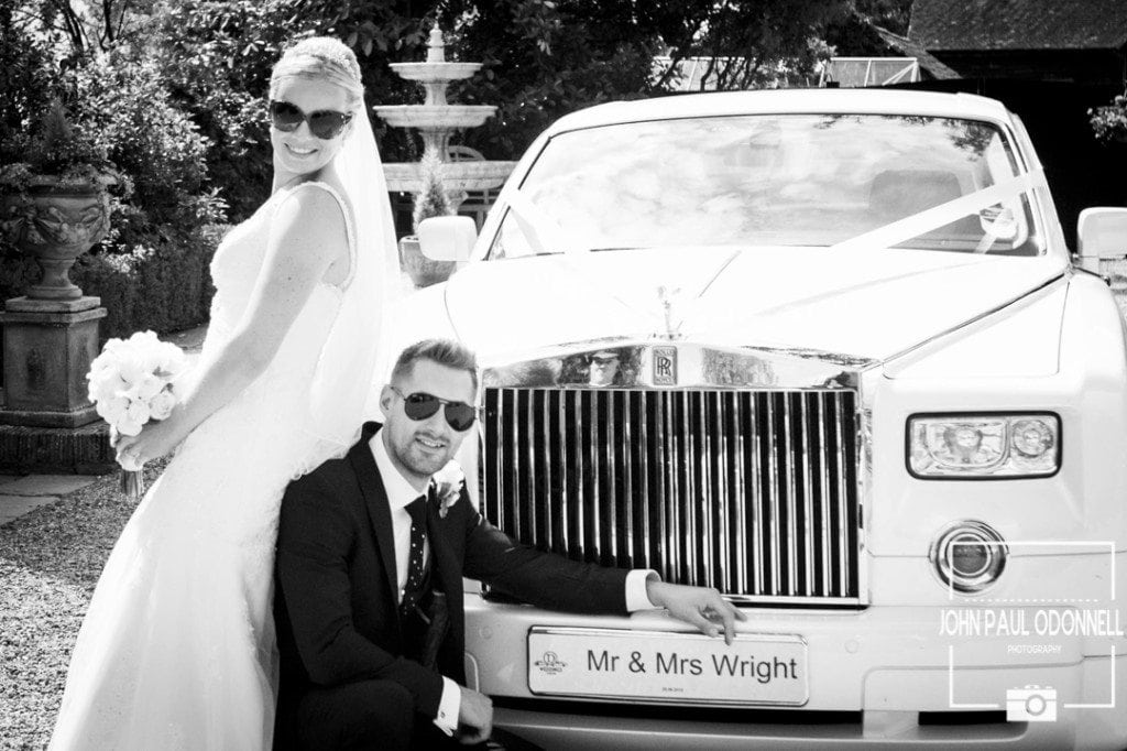 Reportage shot of the bride and groom with a Phantom Rolls Royce