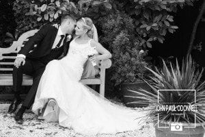 Carly and Matt photographed on the bench at Newland Hall in black and white