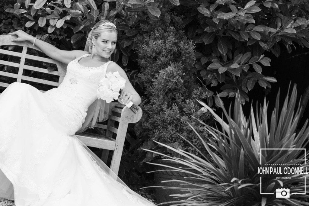 A beautiful Reportage picture of a Bride on a bench posing with her flowers