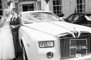 This picture is of the Bride and Groom with a Rolls Royce Phantom taken at the front of Prince Regent Chigwell