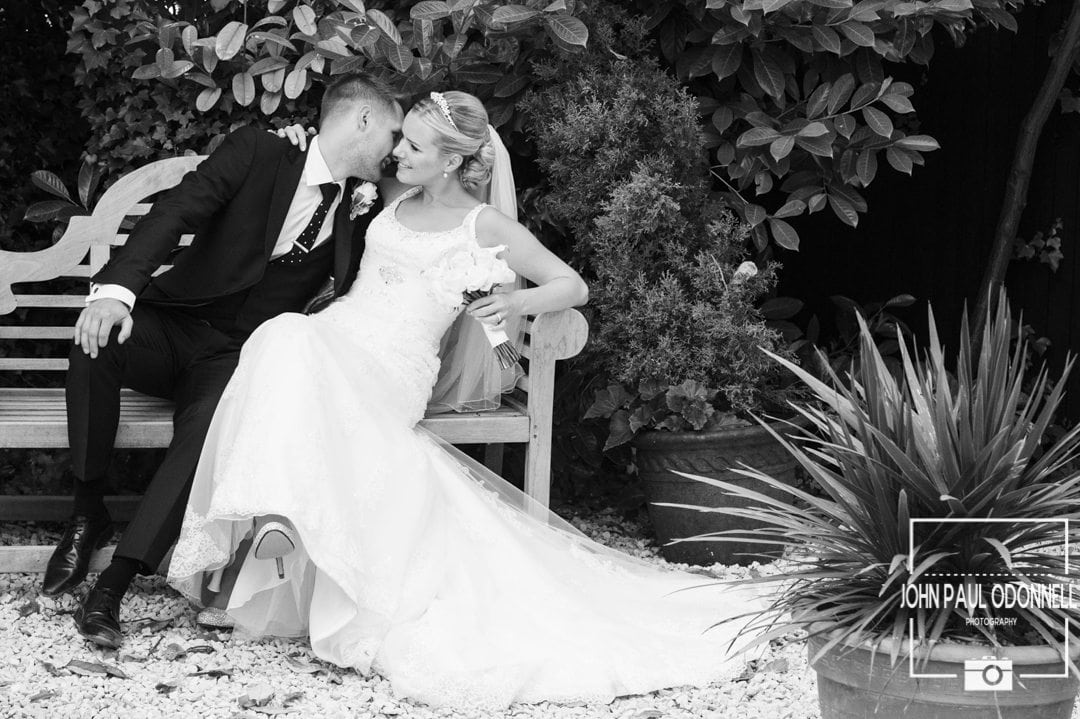 A picture taken in Reportage style of a Bride and Groom Kissing on a bench in black and white