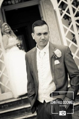 This picture is of Bride and Groom in a classic Reportage picture grey suit
