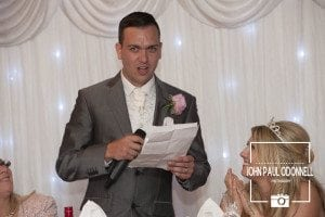 This picture is of a Groom doing his wedding speech at the top table on his wedding day