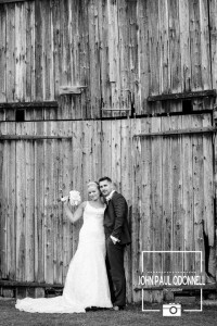 Bride and Groom at the entrance to the the Wooden barn at Newland Hall