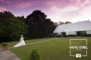 Bride walking to the marquee at Newland Hall beautiful purple sky