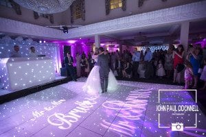 Bride and Grooms first dance at their wedding on led dance floor their names in lights