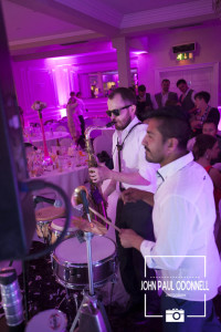 A saxophone and bongos being played on the dance floor at a wedding