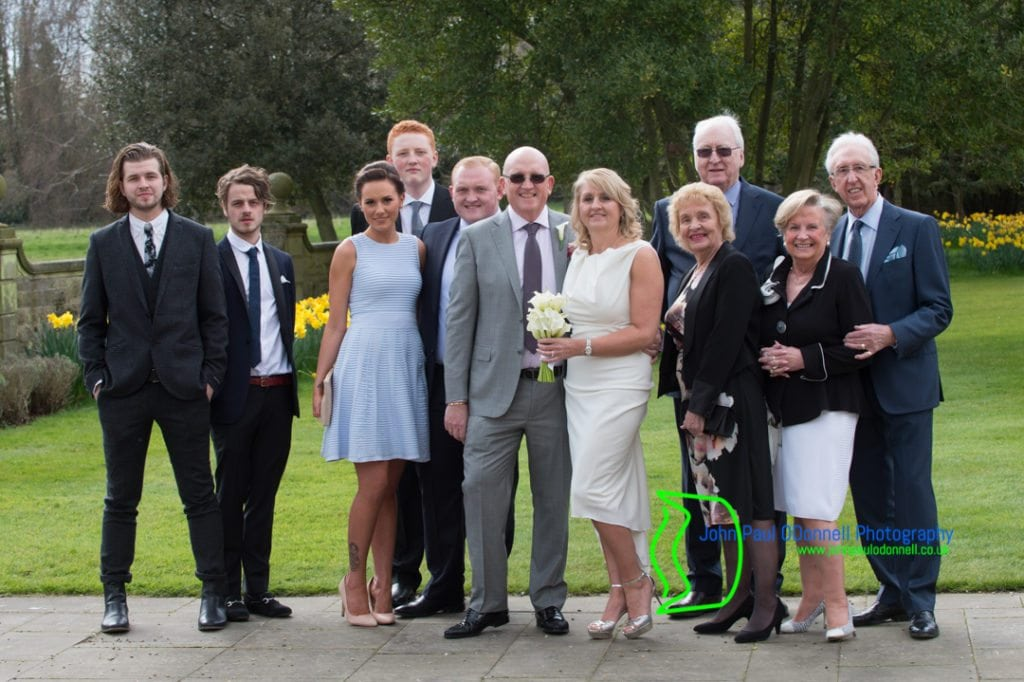 Bride and Groom and family in the gardens of Fanhams Hall