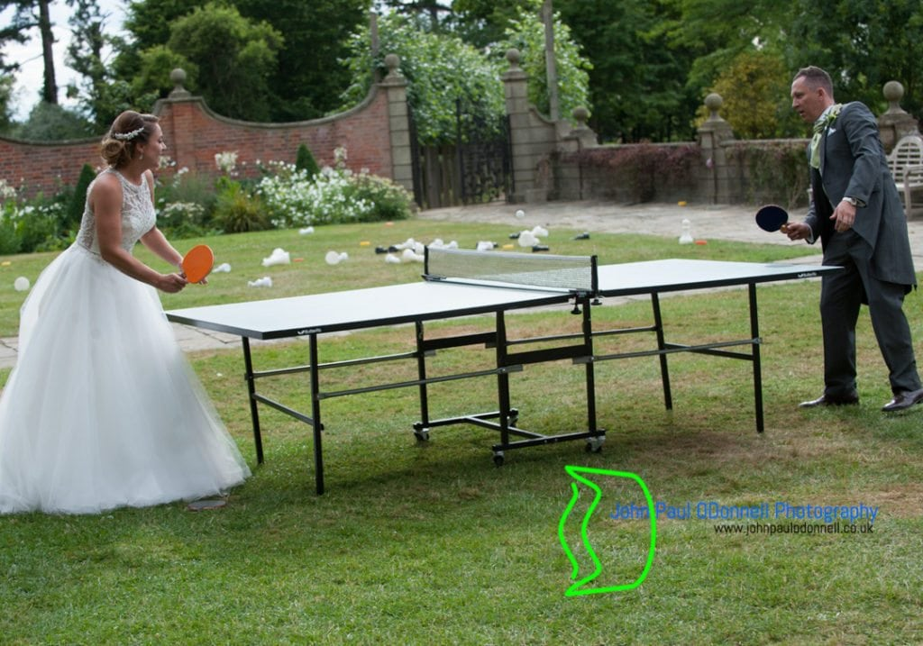 The bride and groom are playing table tennis