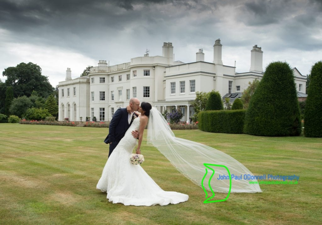 image of the bride and groom outside the mansion house Blake Hall