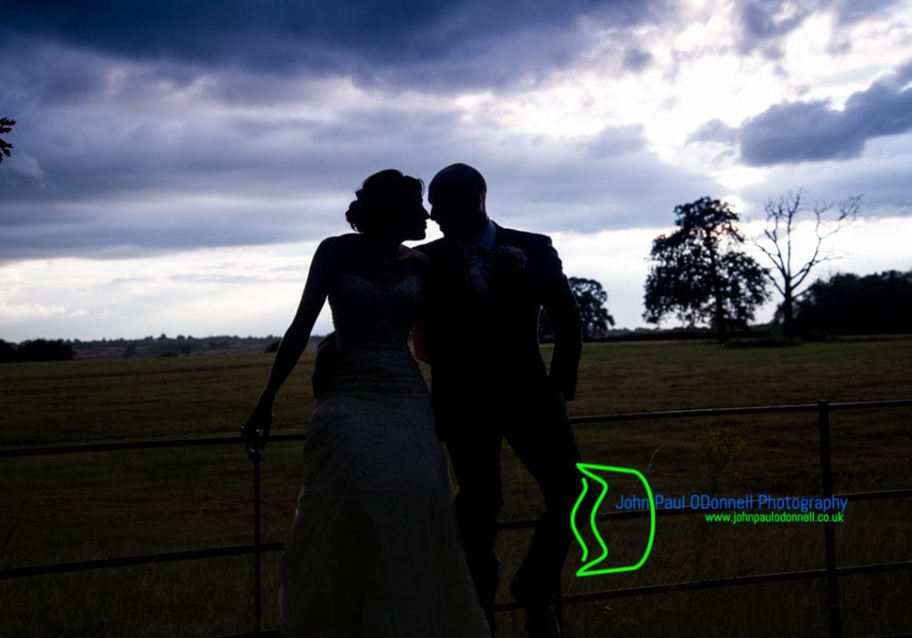 Image of the bride and groom on a fence silouhetted against the purple sky
