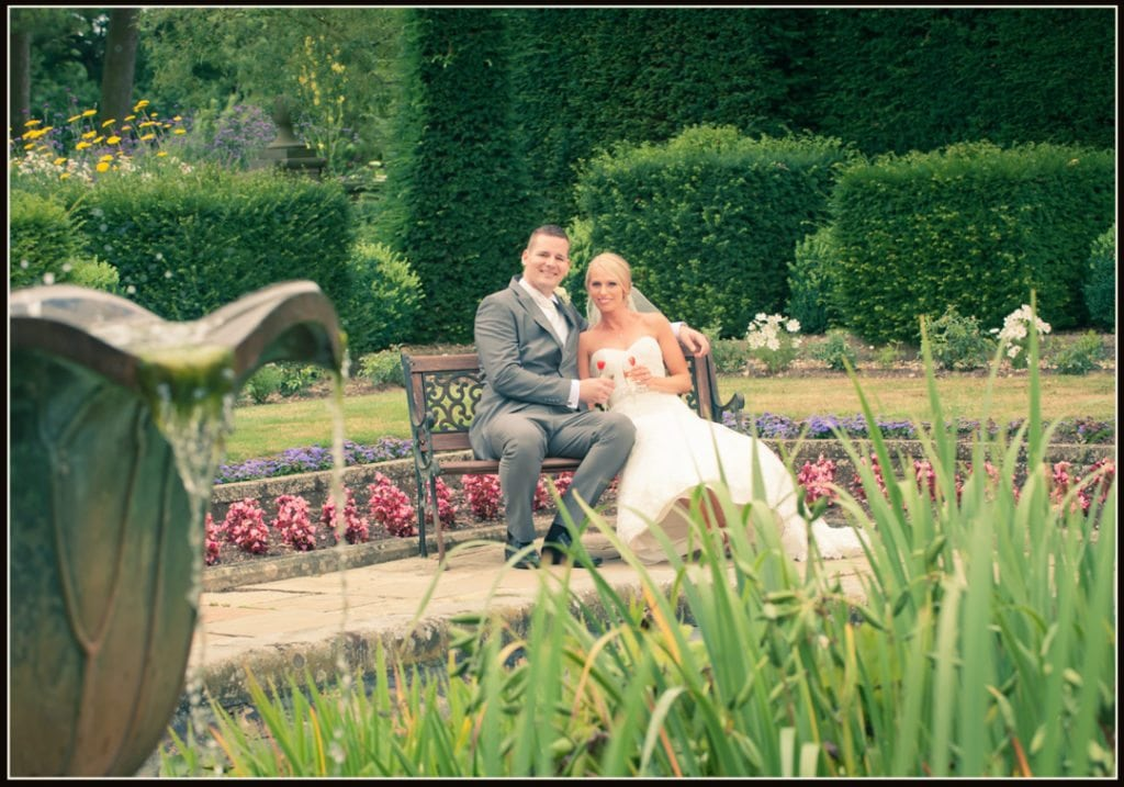 This image is of the bride and groom sitting on a bench by the fountain