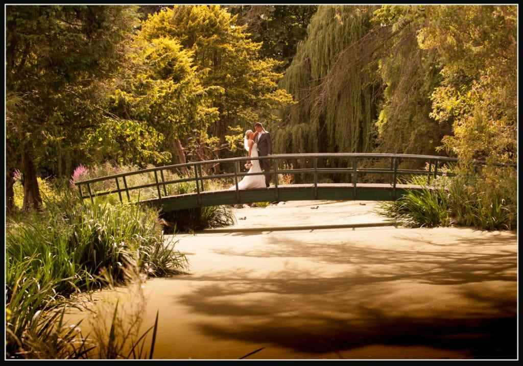 image is of the bride on the green bridge at The beautiful Fanhams Hall Hotel