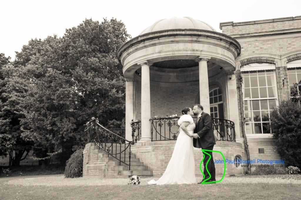 bride and groom kissing in front of ponsbourne park
