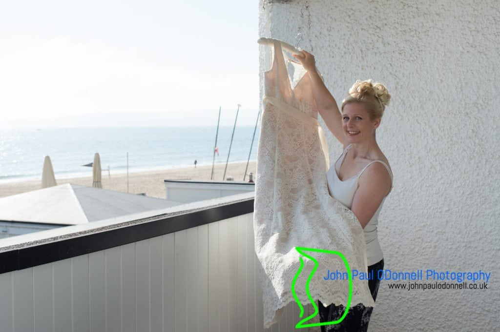 Bride holding her wedding dress by the sea