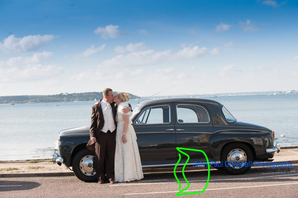 bride and groom kissing by the wedding car by the sea