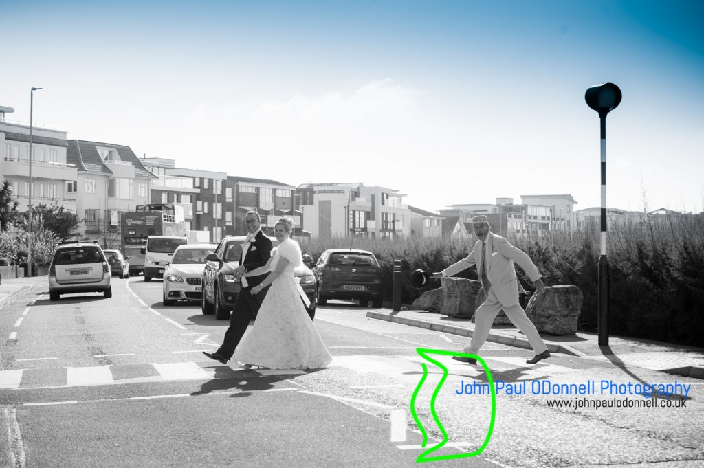 bride groom and a friend using the zebra crossing