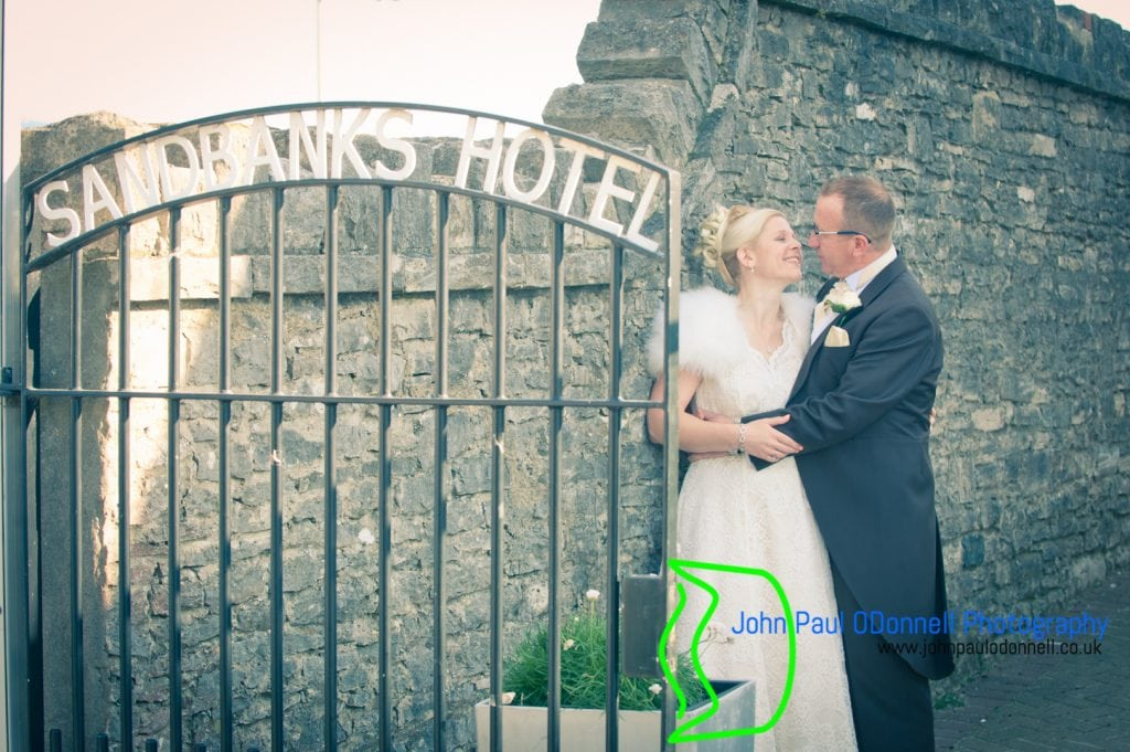 bride and groom about to kiss at sandbanks hotel gate