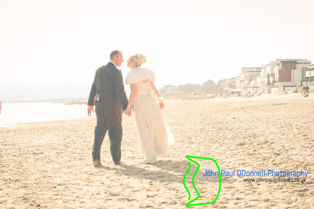 bride and groom on the beach holding hands