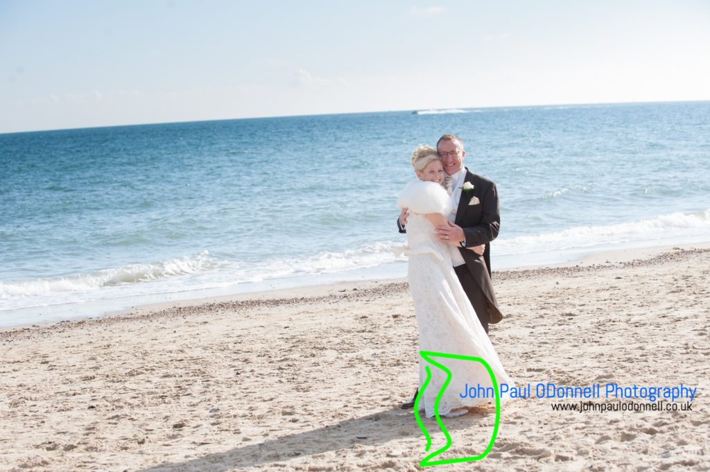 bride and groom on the beach holding