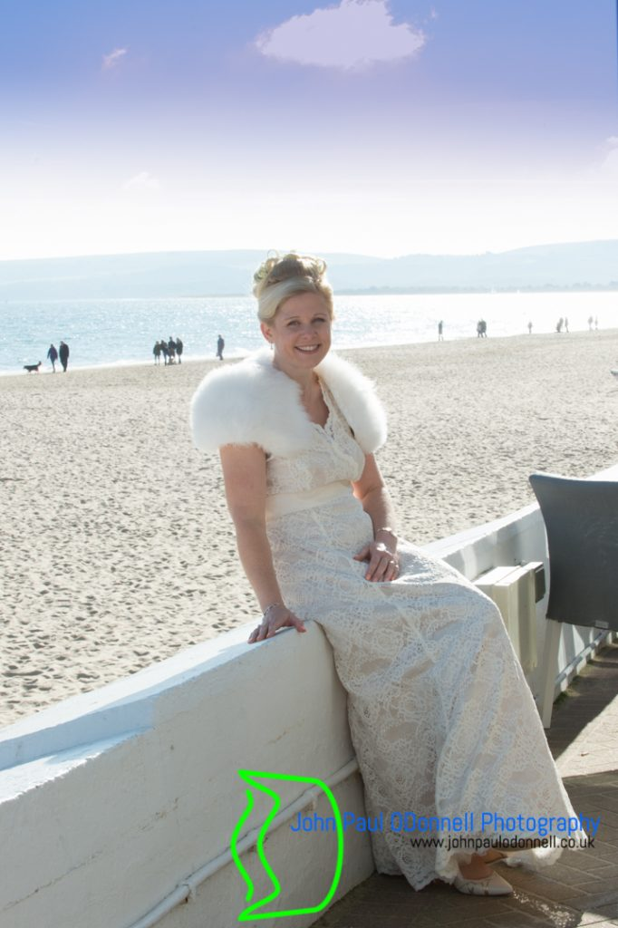 bride by the beach sea behind