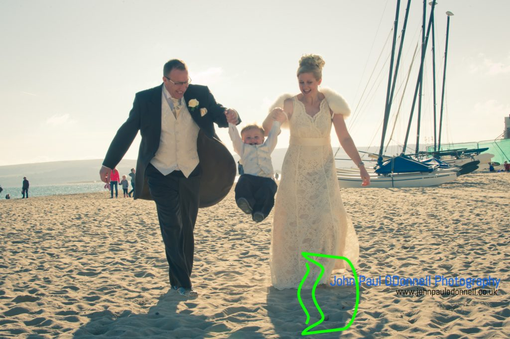 Bride and groom playing with their son whilst holding hands on the beach