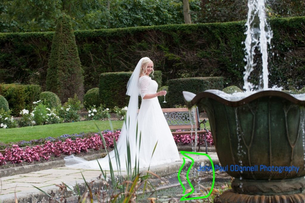 This image is of the bride in her wedding dress by the fountain in the beautiful gardens at fanhams hall