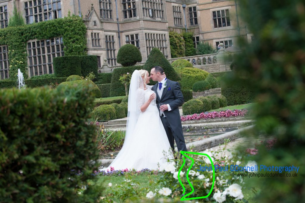 georgie and matthew fanhams hall 14 . This image is of the bride and groom kissing on their wedding day by the fountain and beautiful gardens fanhams hall.