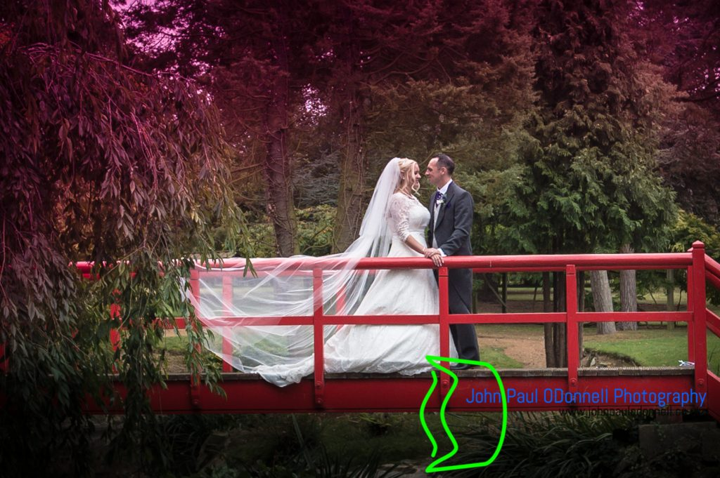 This image is of the bride and groom on the red bridge on their wedding day in the grounds of fanhams hall.