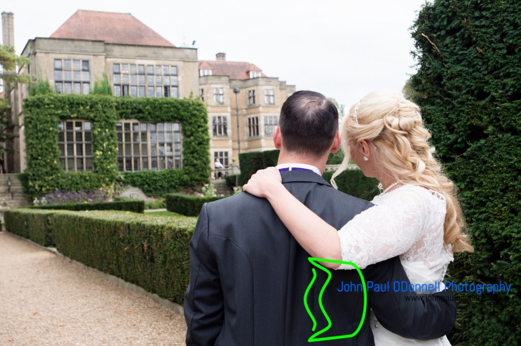 This image is of the bride and groom looking back at the mansion houser on their wedding day at fanhams hall