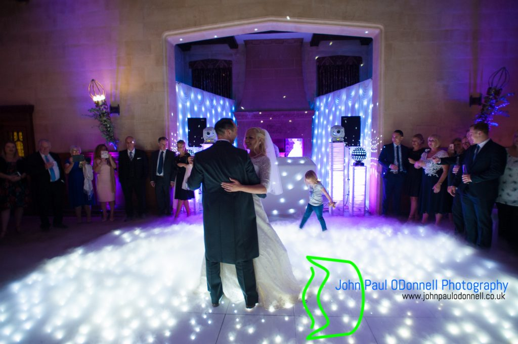 This image is of the bride and groom doing their first dance in the great hall at Fanhams Hall Hotel Hertfordshire