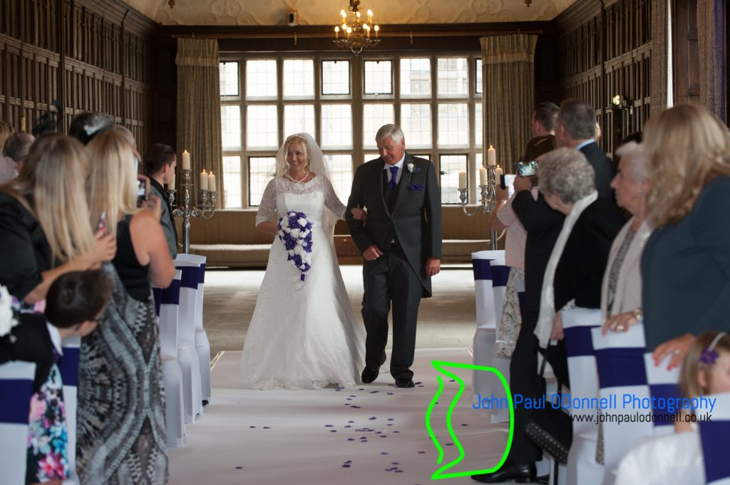 This is an image of the bride and her dad walking down the aisle of the long gallery at the hotel.