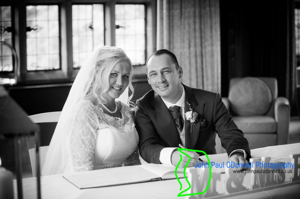 This image is of the bride and groom signing the register in a civil ceremony in the long gallery at fanhams hall hotel.