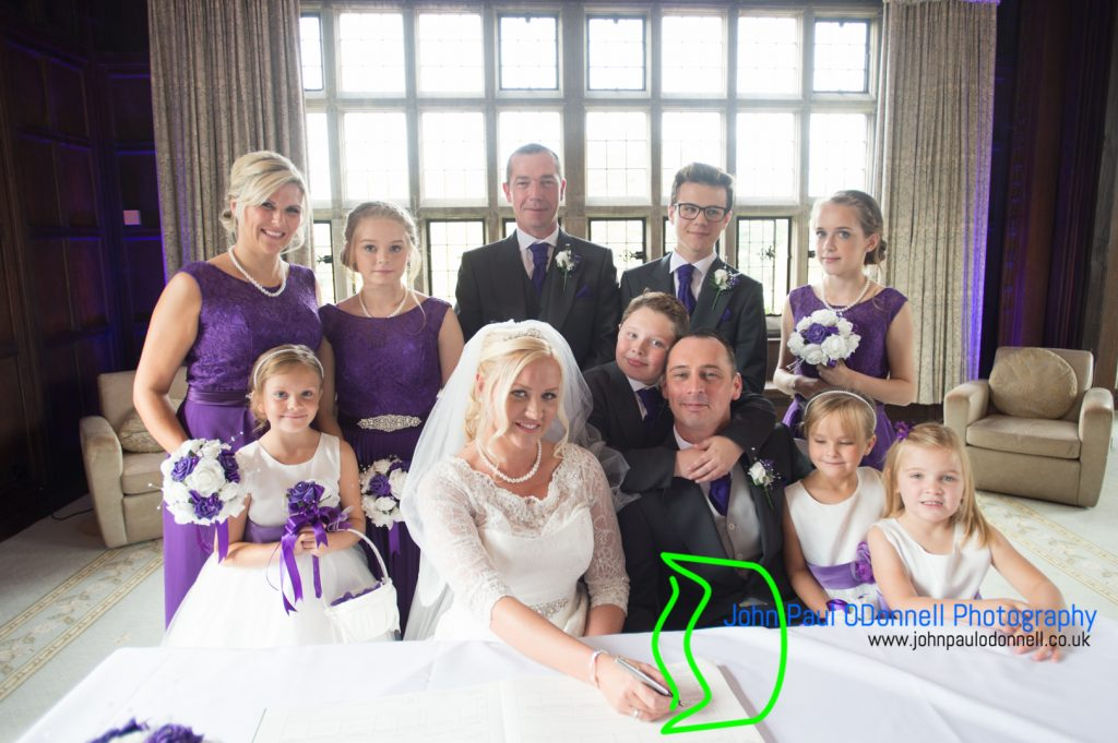 This image is of the bridal party signing the register in the long gallery at fanhams hall hotel.