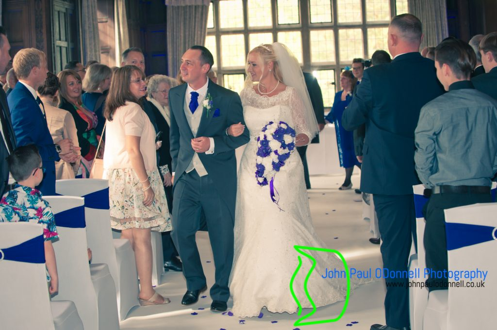 This image is of the bride and groom walking down the aisle in the long gallery at fanhams hall hotel.