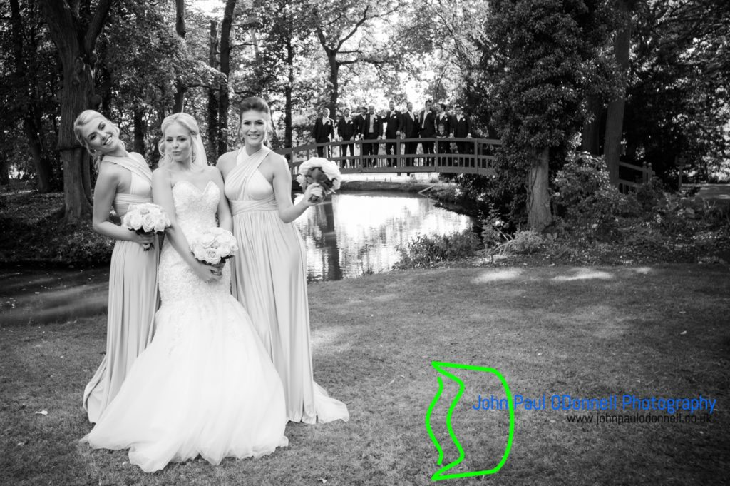 Bride and bridesmaids by the bridge at mulberry house