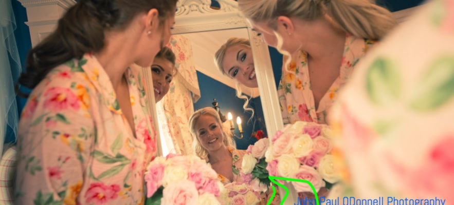 Bride and bridesmaids in the mirror in the bridal suite at mulberry house